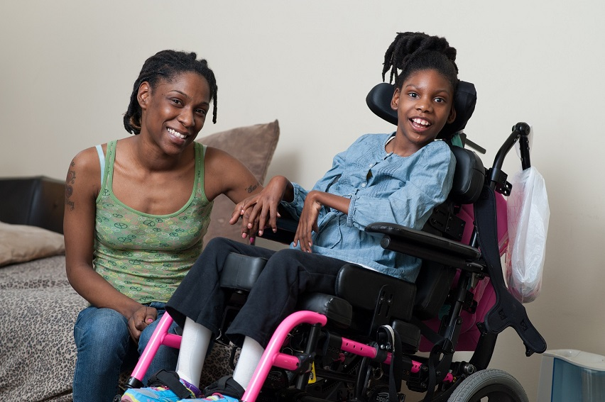 Photo of Client Towanna R. and her daughter. Towanna is sitting beside her young daughter's wheelchair and both are smiling.